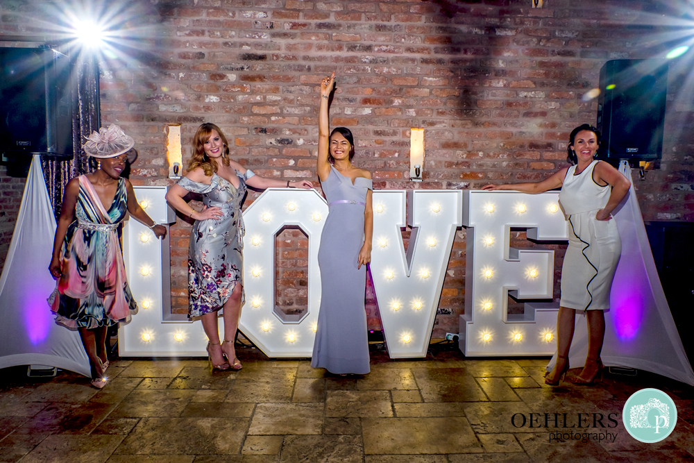 Bridesmaids and guests posing in front of the Love Sign