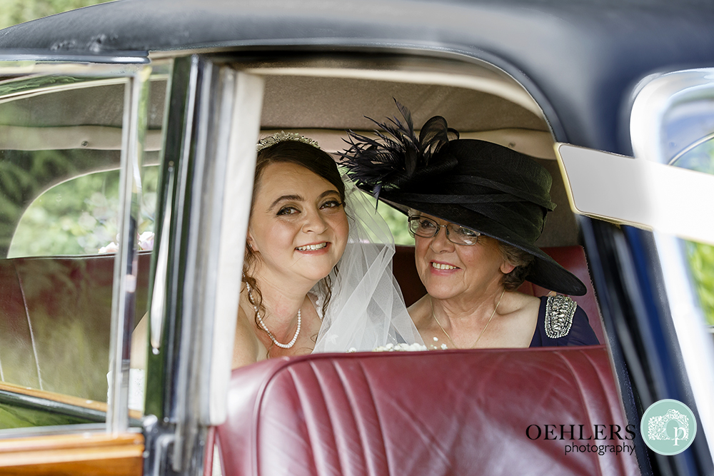 bride looking out of car with mum at her side