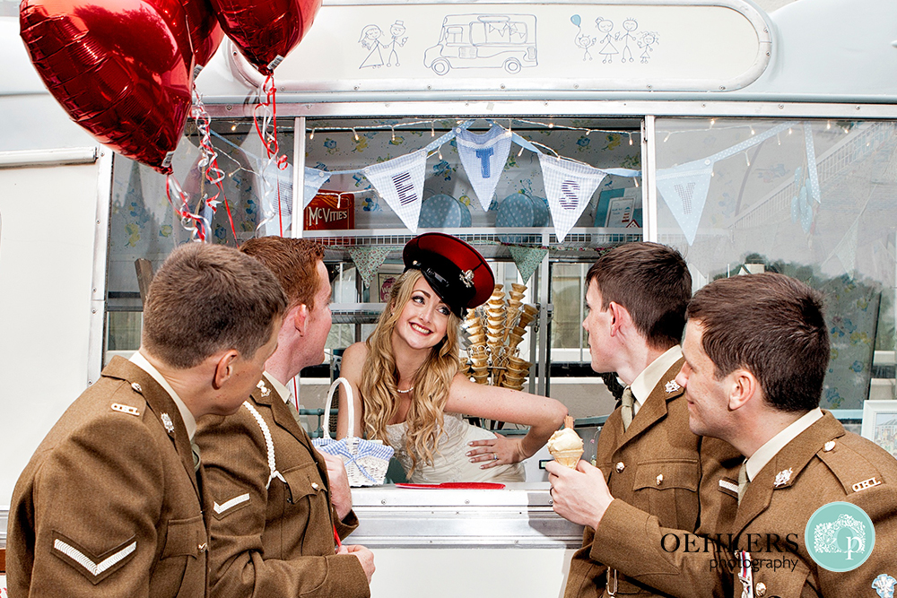 Bride inside an ice cream van posing whilst the groom and his grromsmen look on