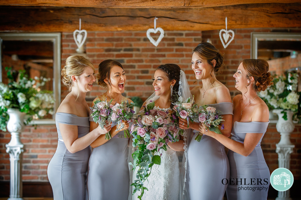 Brides laughing and looking at bride in a group photograph