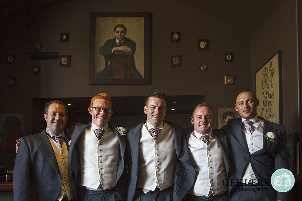 Groom with groomsmen posing in the bar at Stubton Hall