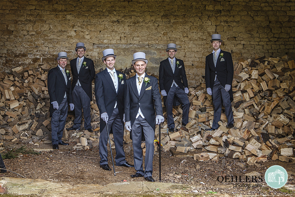 Groom and groomsmen posing on a log pile in a barn