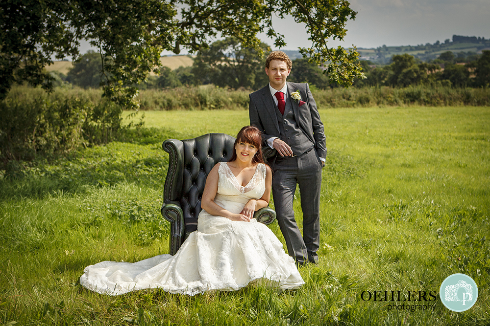 Bride sitting on an armchair whilst grrom leans on it behind in the beautiful countryside.