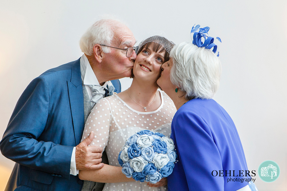 Parents kissing their daughter on the cheek