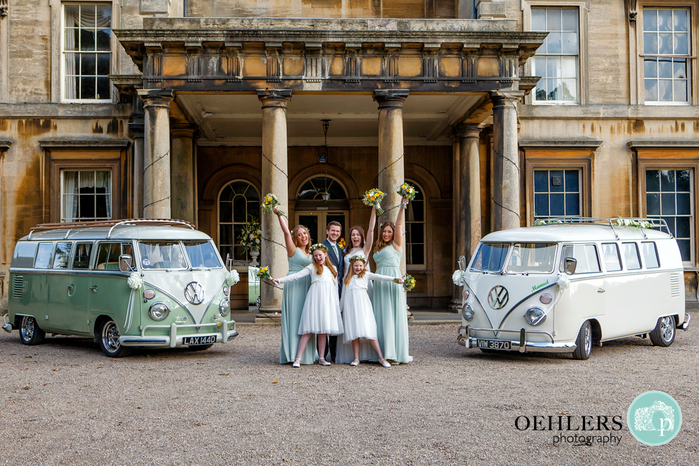 Bridal party outside Preswold Hall in between two camper vans.