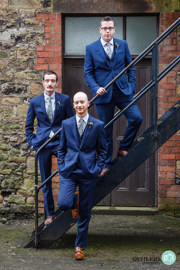 Groom posing with bestmen on metal staircase outside