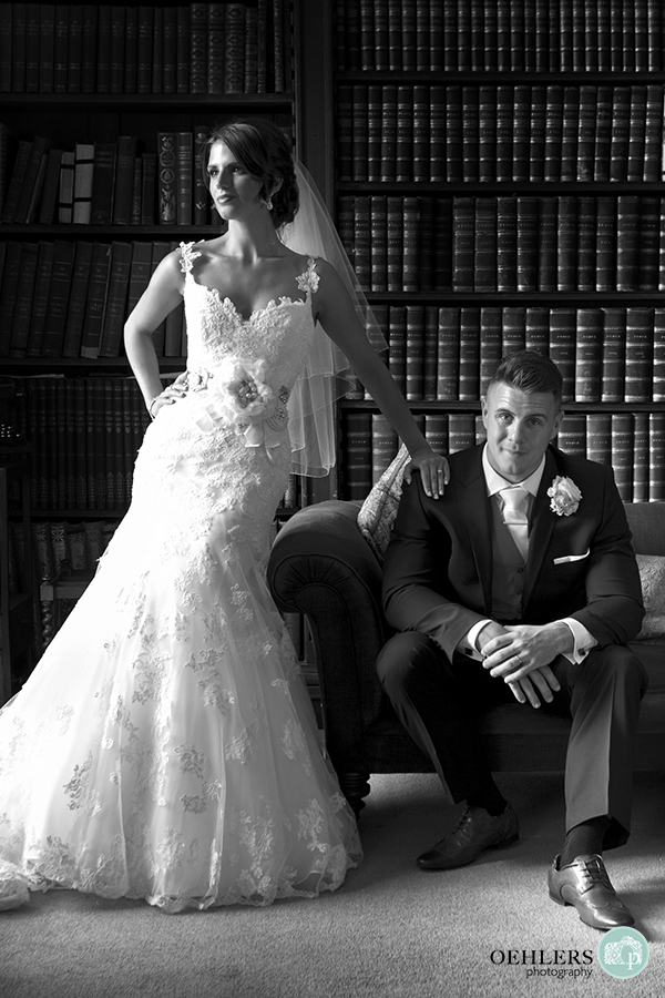 Groom sitting on an armchair whilst bride stands with hand on his right shoulder