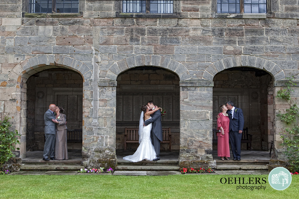 Three archways of building, bride and grrom in middle kissing and their parents on either side kissing
