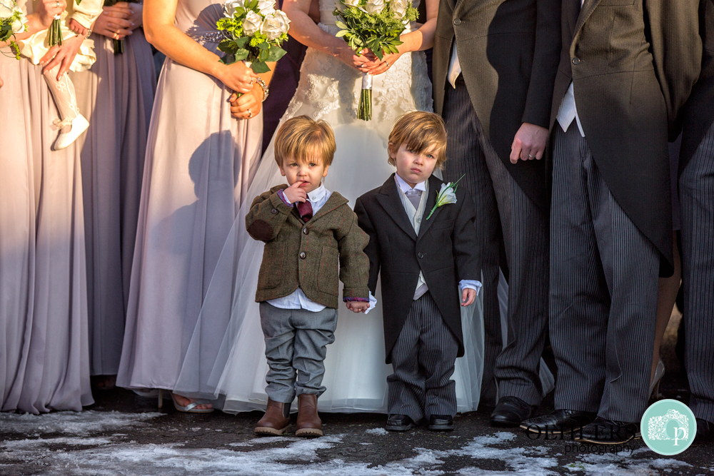 Cute photograph of Page Boy holding hands with best friend in front of group shot.