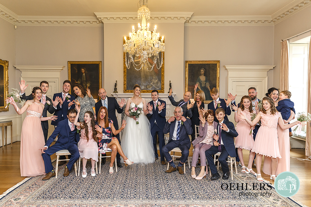 Indoor big group photograph of bride and groom with their families