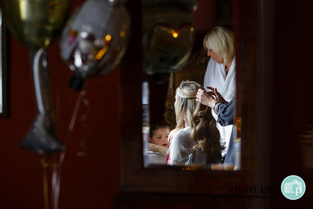 reflection of bride getting ready in the mirror