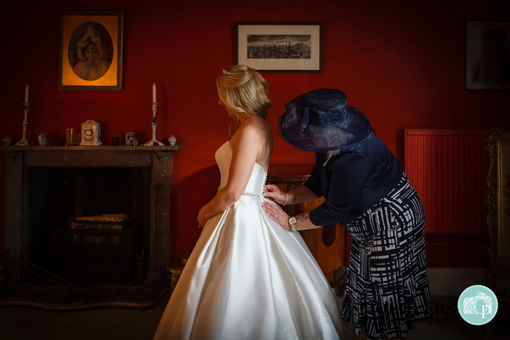 mum doing up daughters wedding dress