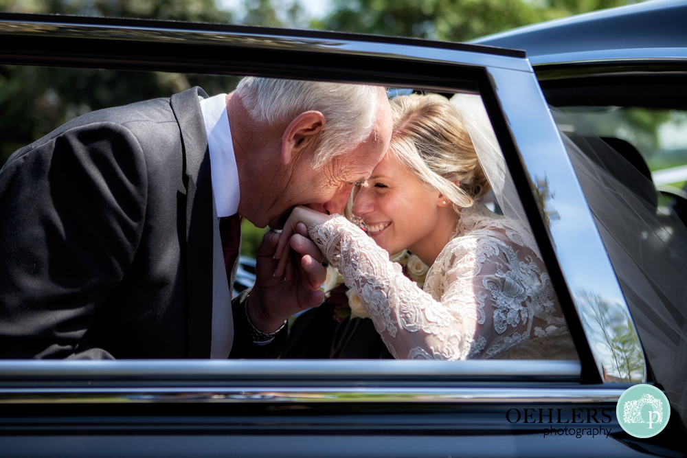 dad kissing hand of bride whilst getting her out of car