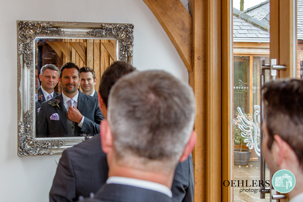 groomsmen looking at themselves in the mirror
