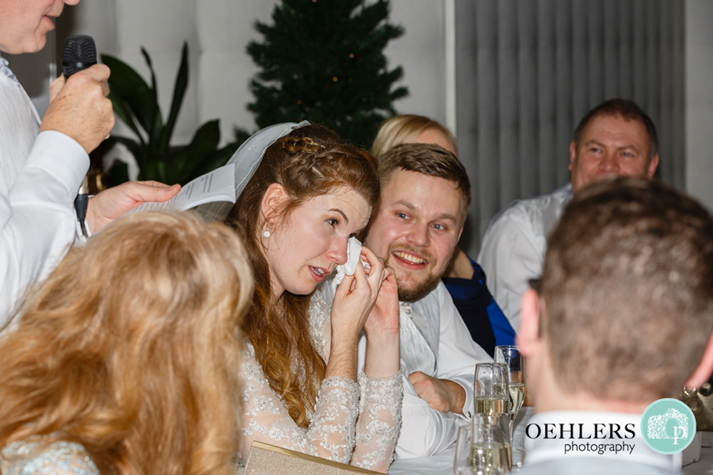Bride wiping her teary eye whilst her Groom makes a speech