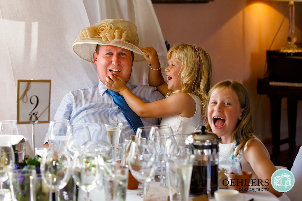 Children laughing whilst putting a hat on their dad.