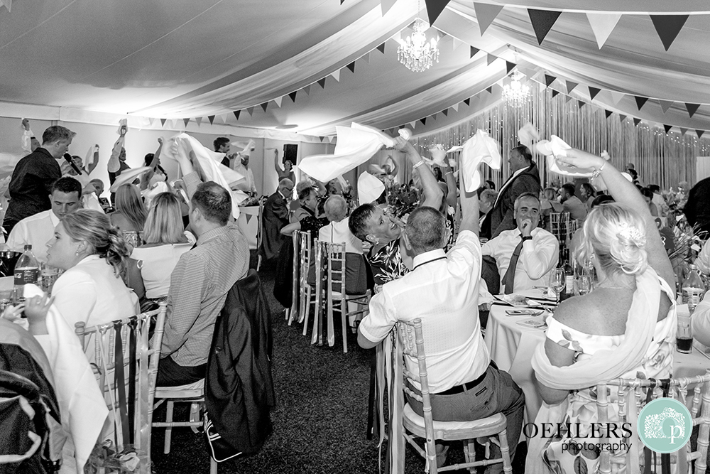 Guests waving their serviettes whilst the singing waiters perform