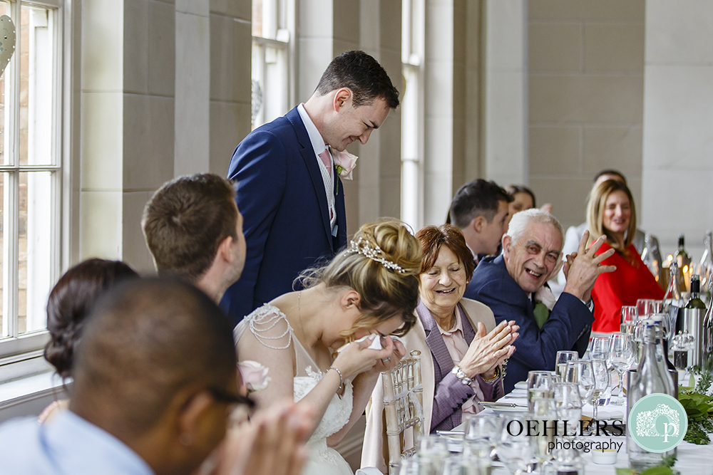 Groom making a funny speech whilst bride cries with laughter
