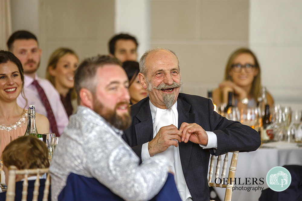 Uncle with moustache and pointed beard laughing at a speech