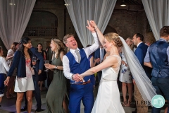 Bride dancing with guests with arms out