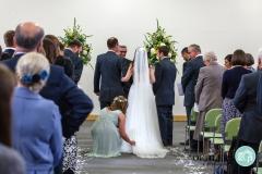 bridesmaid arranging brides train in the ceremony