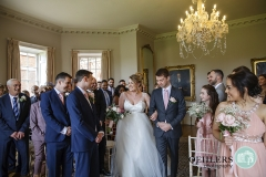 bride happy to see groom at end of aisle