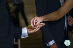 bride picks up wedding ring from a tray