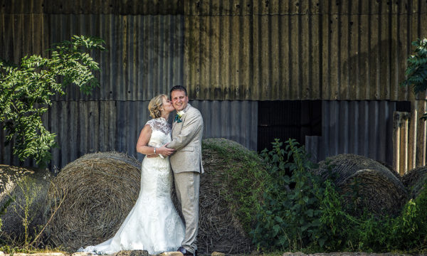 Bride and Groom in front of rustic background