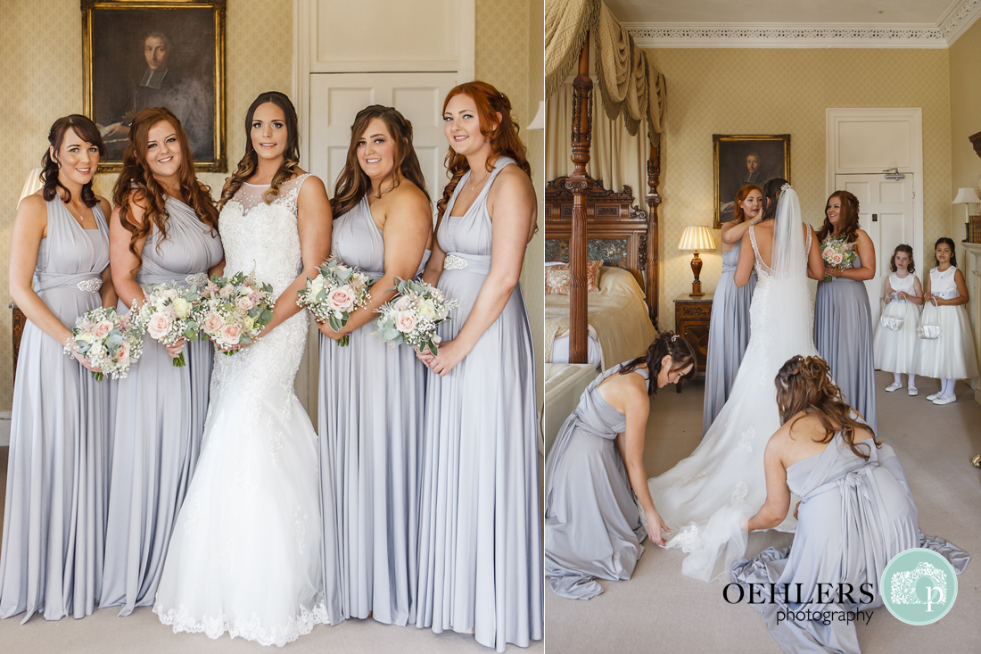 Bride and Bridesmaids posing and arranging brides wedding dress.