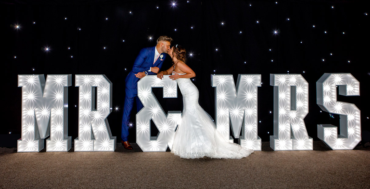 Nottingham Wedding Photographers-Bride and Groom kissing at Mr and Mrs lights
