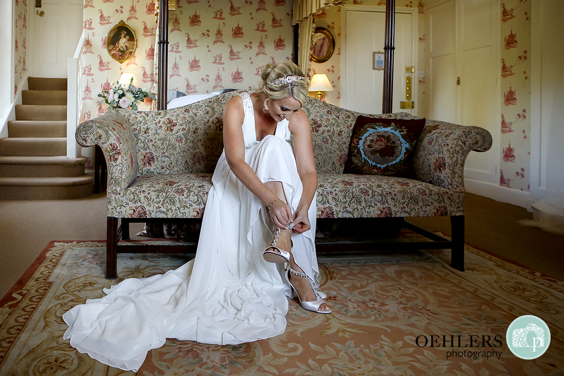 Bride elegantly putting on her shoes