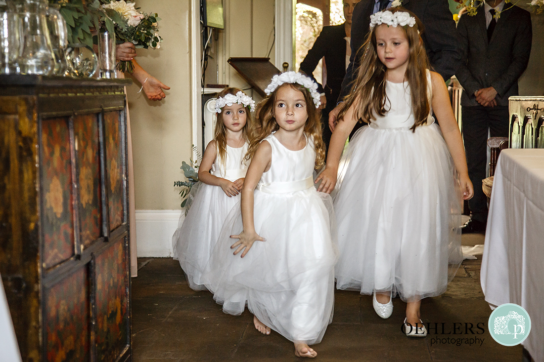 Flowergirls running to greet the bride