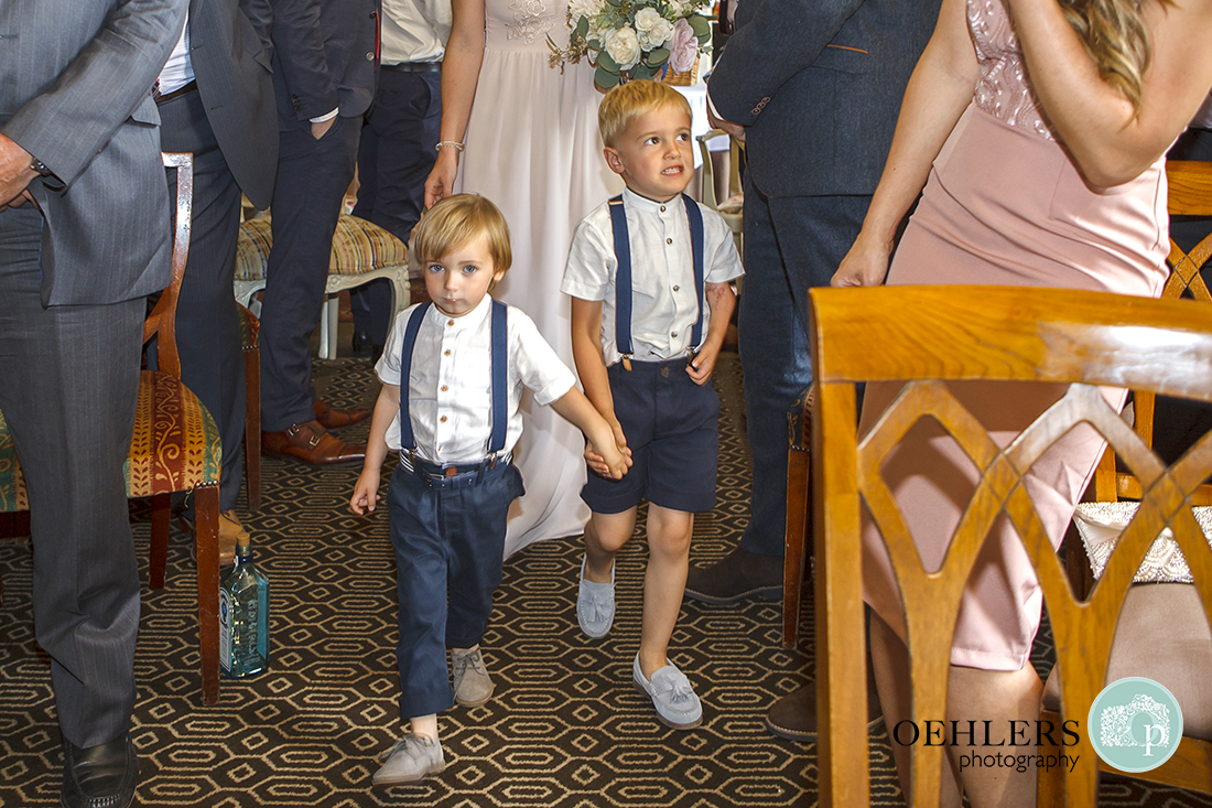 Page boys reluctantly walk down the aisle