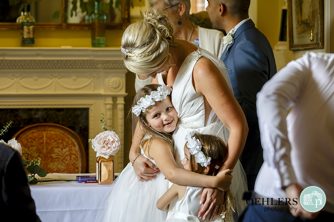 Flowergirls hug the Bride through happiness