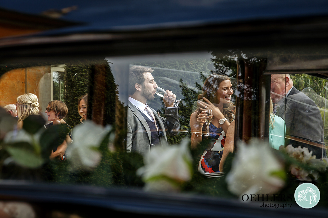 Guests enjoying a drink through the window of the wedding car