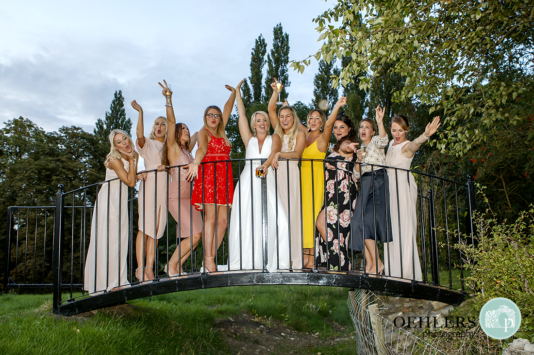 Bride and her happy friends on the bridge