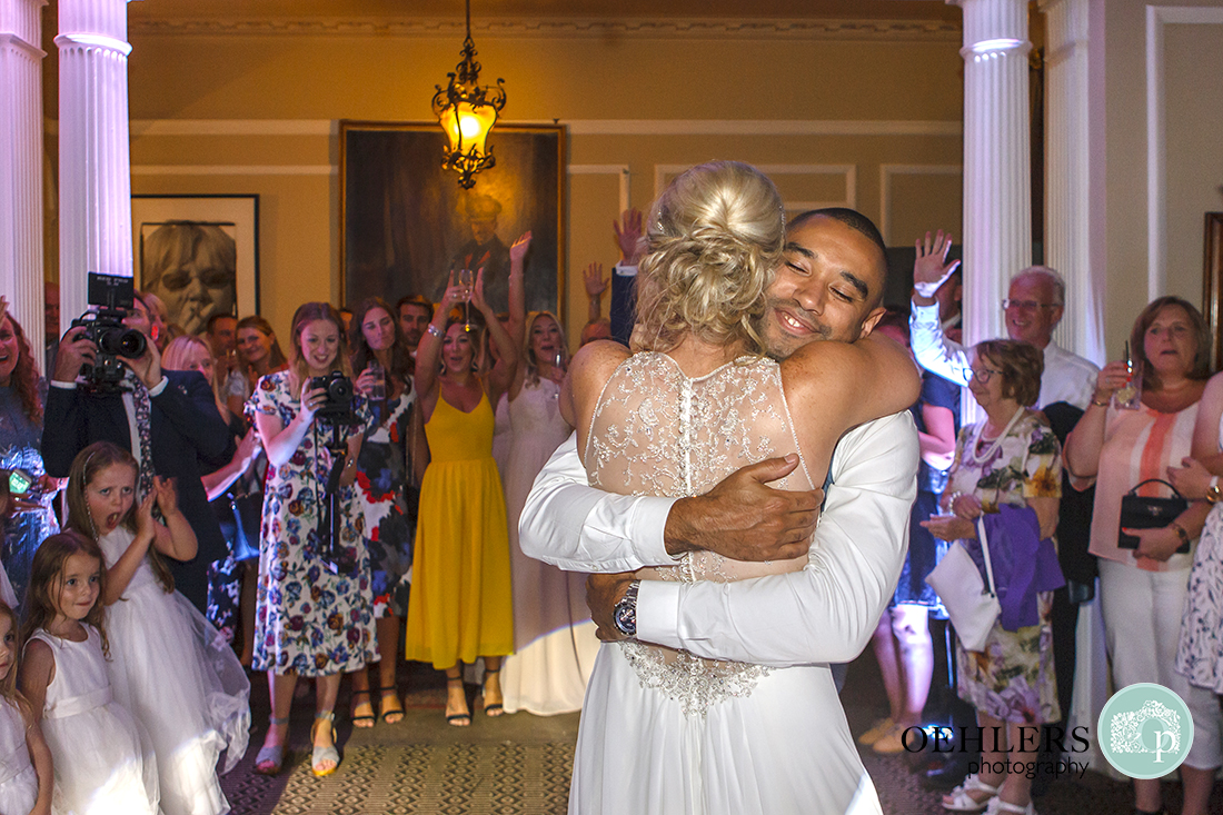 Groom gives his wife a huge hug at the end of the first dance