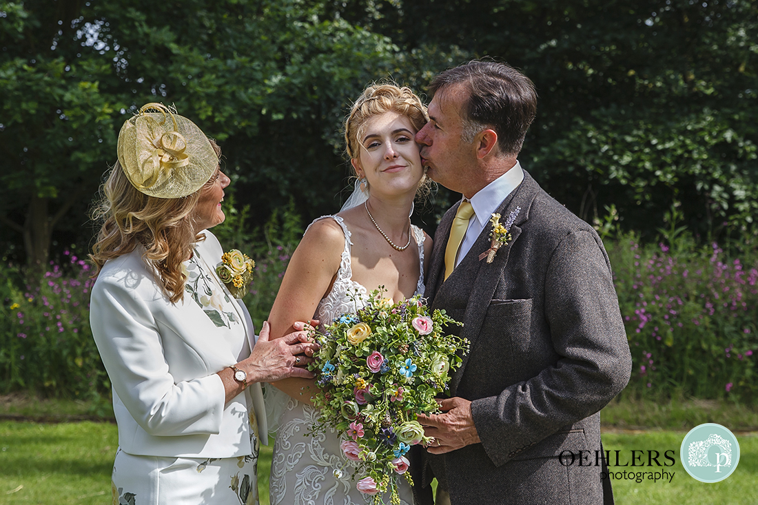 Brides parents with dad kissing the bride on her cheek