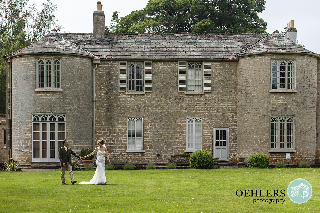 Bride and Groom walking in front of Cockliffe House