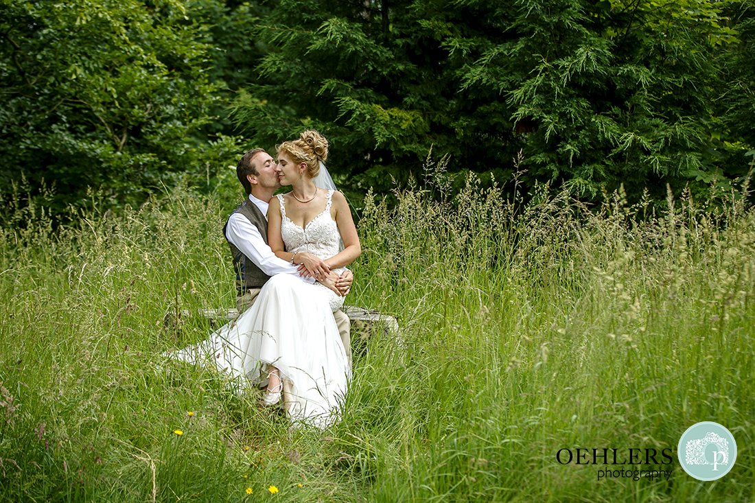 Bride sitting on Groom's lap in the grass