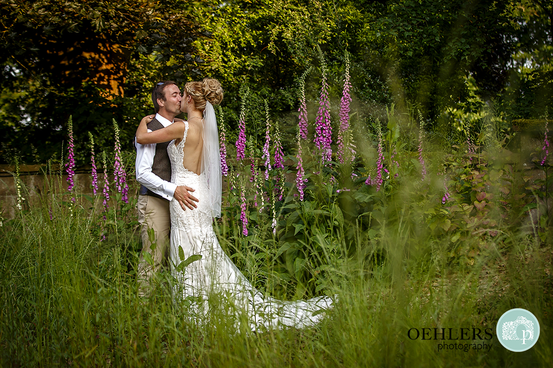 Bride and Groom having a kiss in the foxglove garden