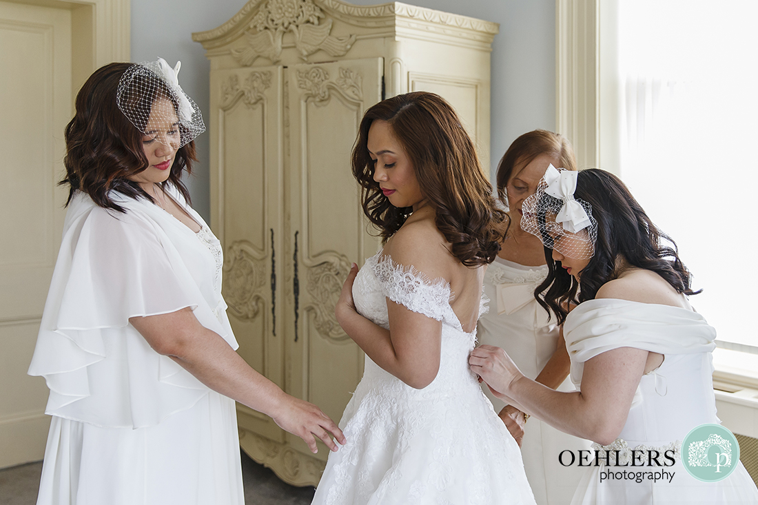 Bridal party helping bride with the wedding dress