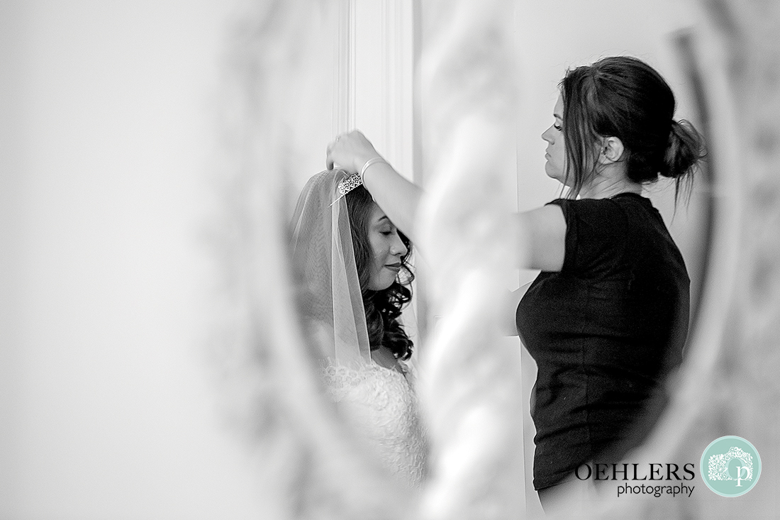 reflection of the bride putting her veil on