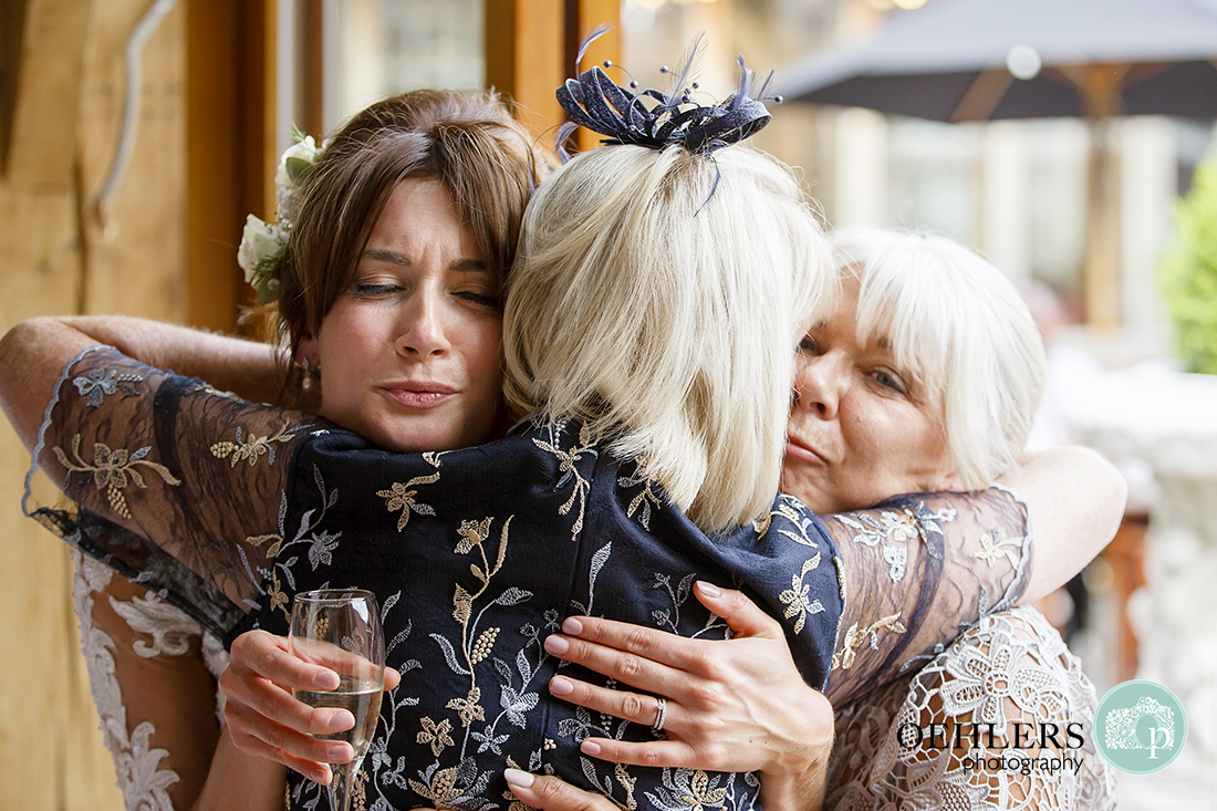 Bride having a huge cuddle from mum and aunty