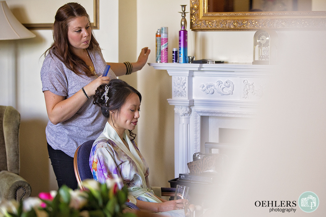 Hairdresser adding finishing touches to the brides hair.