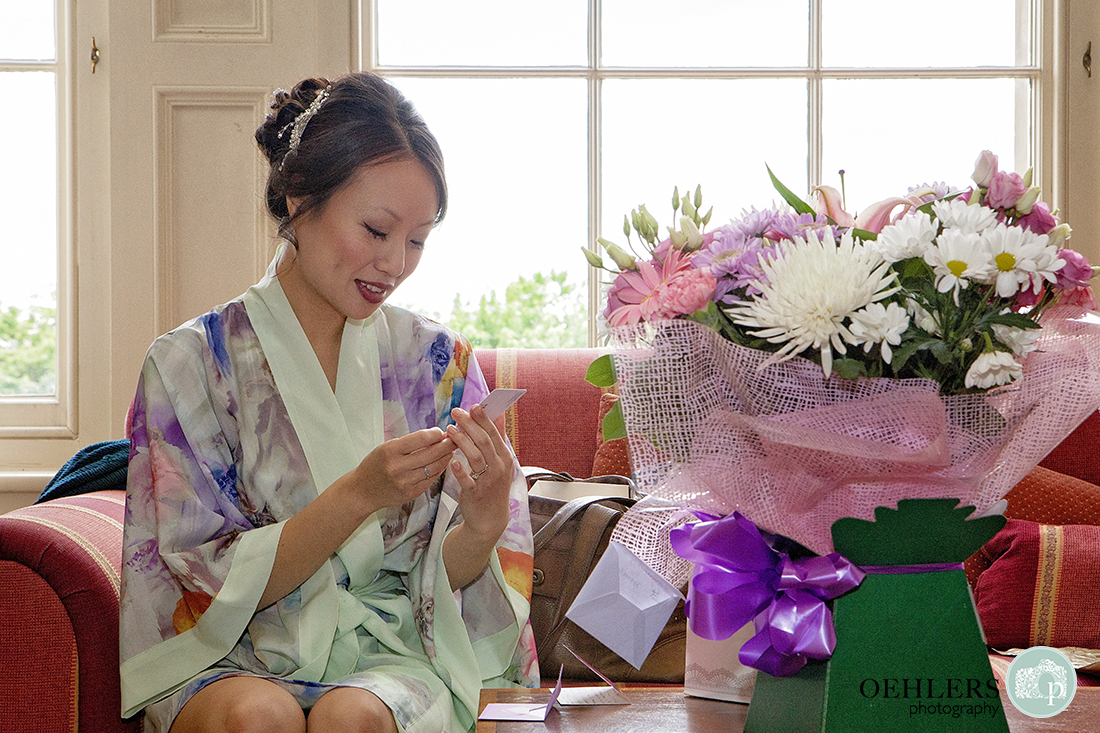 Emotional bride reading a card belonging to the flowers her groom sent her.