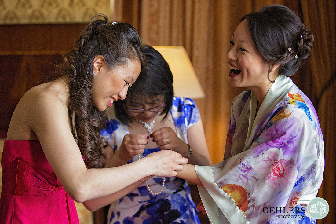 Maid of Honour and Bride laughing as a bracelet is being put onto the bride's wrist whilst mother of the bride struggles with necklace in the background.