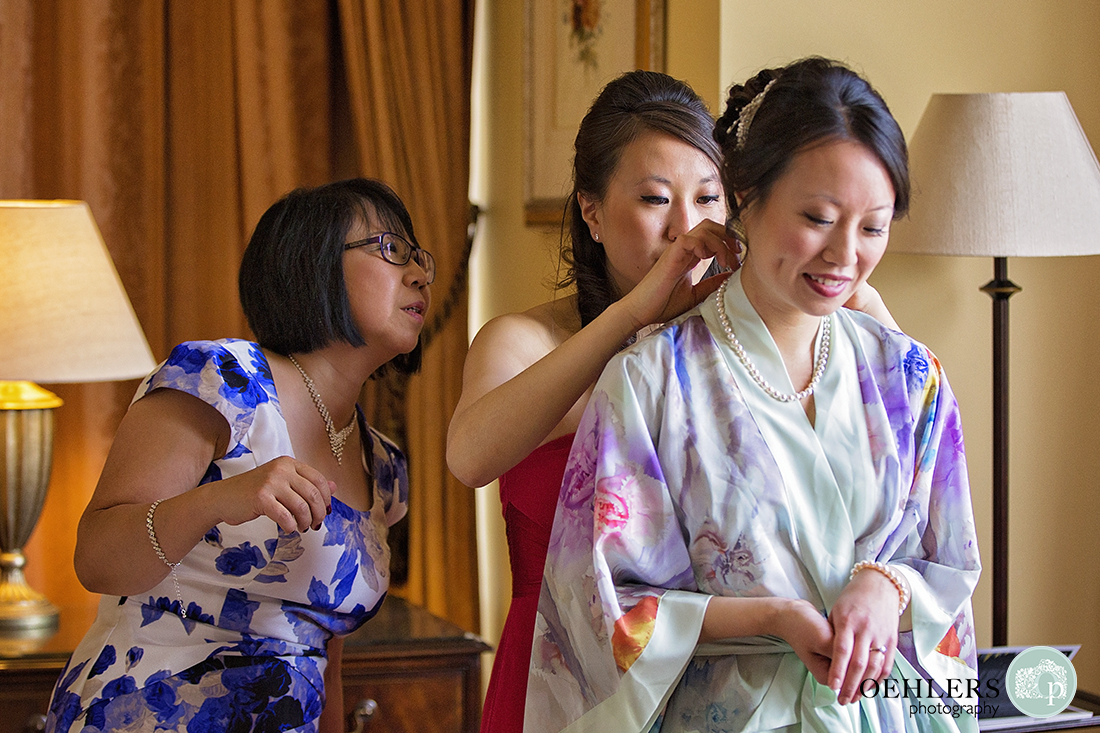 Maid of Honour puts necklace around bride's neck whilst mother of the bride looks on.