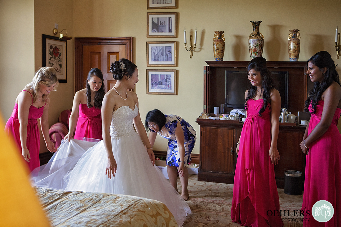 Bride standing with dress on whilst two bridesmaids and mother adjusts the train and the other two bridesmaids look on with laughter.
