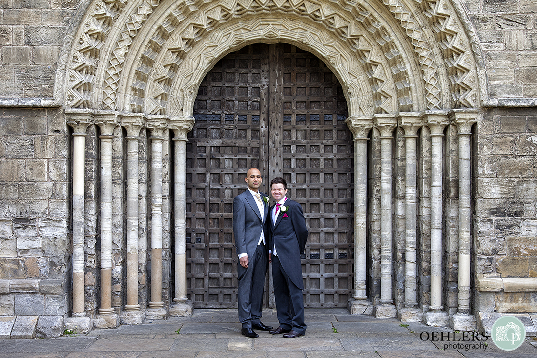 Groom and bestman posing in front of the beautiful entrance of Selby Abbey.